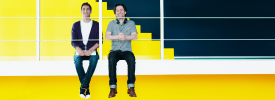 在黃色背景辦公室中的兩個快樂男人